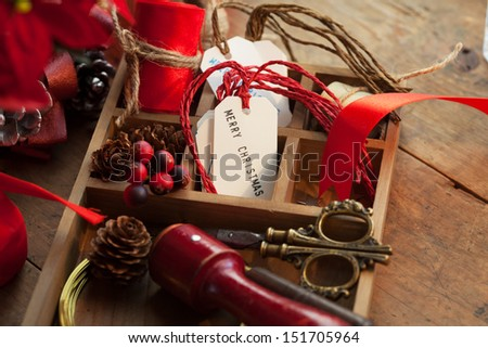 Christmas preparation. Tray with ribbons and christmas tags, on an old wooden table with vintage feel.  - stock photo