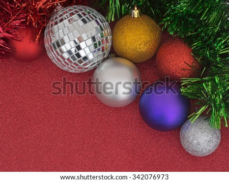 Christmas preparations, background with baubles and green glitter. Red glittery background.