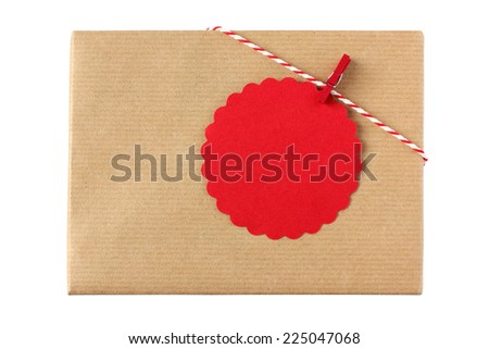 Christmas present decorated with red twine and red gift tag with copy space - isolated on white background - stock photo