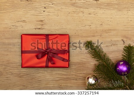 Christmas present, fir twigs and baubles on wood - stock photo