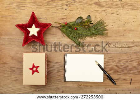 Christmas present, notepad and fir twig on wood - stock photo