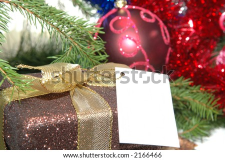 Christmas present with empty card under tree close up