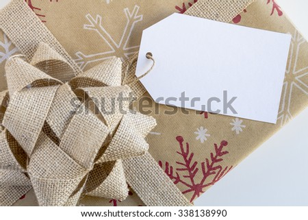 Christmas present wrapped in brown wrapping paper with snowflakes, brown burlap bow and blank tag sitting on white background
