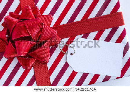 Christmas present wrapped in red and white striped wrapping paper red ribbon and bow and blank tag sitting on white background - stock photo
