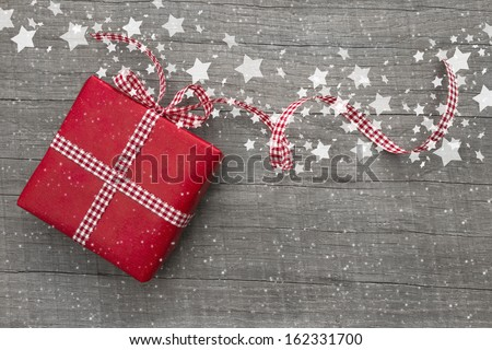 Christmas Present wrapped in red paper on a wooden background for a voucher coupon - greeting card country style - stock photo