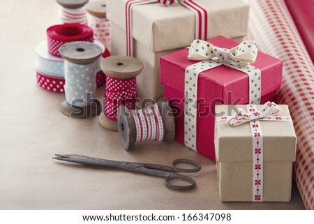 Christmas present wrapping background, wooden vintage ribbons spools and gift boxes and wrapping paper rolls - stock photo