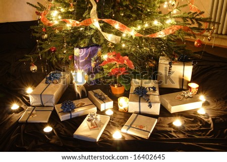 Christmas presents and candles under the tree