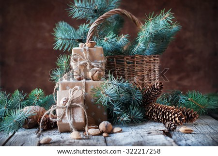 Christmas Presents. Boxes, Coniferous, Pine Cones, Fir Tree, Basket, Walnuts, Almonds on Dark Wooden Table. Still life in Vintage Style - stock photo
