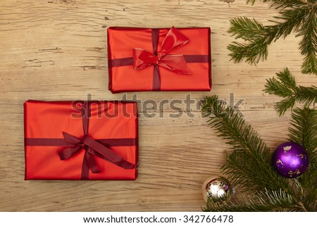 Christmas presents, fir twigs and baubles on wood - stock photo
