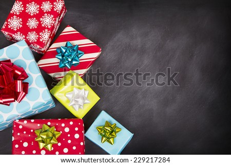 Christmas presents grouped around a chalkboard - stock photo