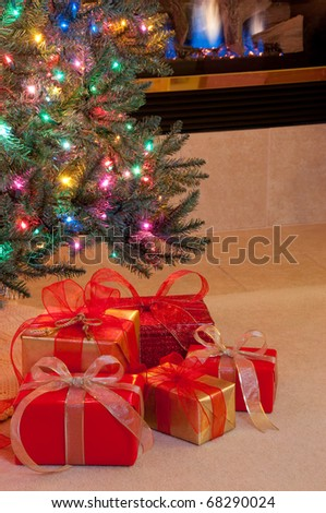Christmas presents in red and gold under tree by fire - stock photo