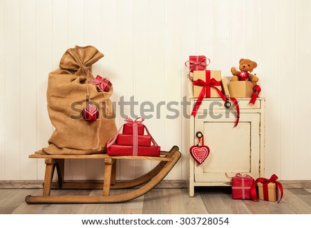 Christmas presents in red and white in vintage style on old wooden background with sledge. - stock photo