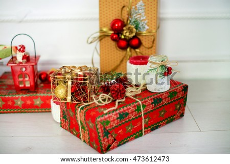 Christmas presents in red paper, decorated with cones, balls and branches snow