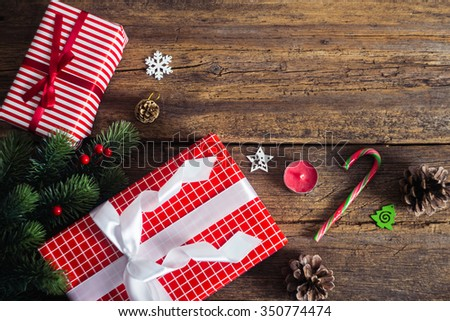 Christmas presents on a wooden background with candy cane, fir branches, candle, cones. - stock photo