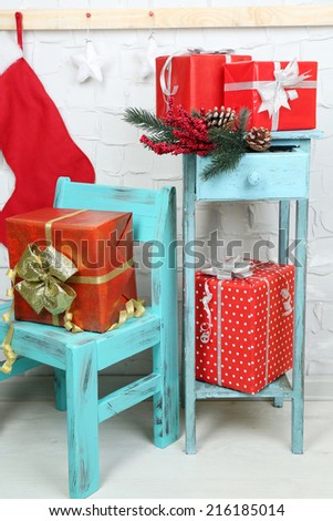 Christmas presents on blue chair and bookcase on brick wall background