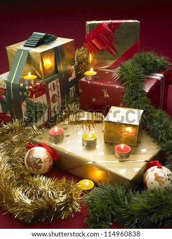 Christmas presents with candles, tinsel and baubles in a festive scene - stock photo