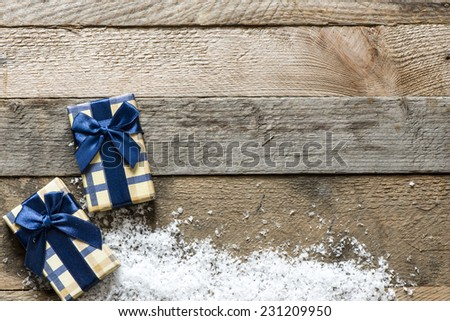 Christmas presents with decorative snow on wooden background - stock photo