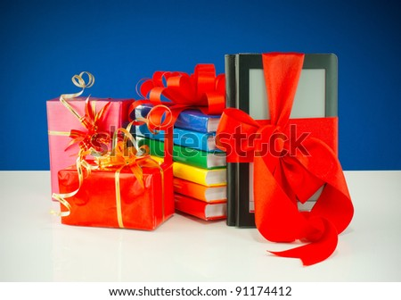 Christmas presents with electronic book reader against blue background - stock photo