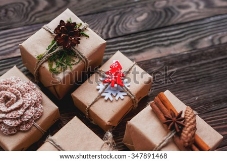 Christmas presents with hand made decorations - crocheted flower and snowflake, pine cones, vanilla pods. DIY decorations for wrapped in craft paper gifts. Place for text. - stock photo