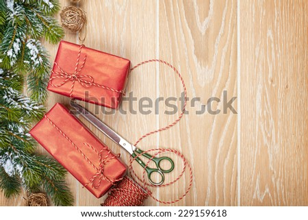 Christmas presents wrapping and snow fir tree over wooden table background with copy space - stock photo