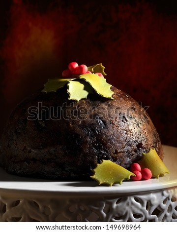 Christmas pudding decorated with holly and berries crafted from icing - stock photo