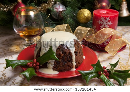 Christmas pudding with white vanilla sauce on holiday table, decorated with holly twig, glass of brandy, ornaments, candles, and xmas tree.  - stock photo