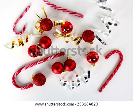 christmas red balls, bright gold and white bows and candy-cane on white surface, top view - stock photo