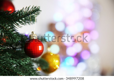 Christmas red bauble on a fir tree over blurred background - stock photo