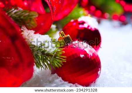 Christmas Red Baubles on snow background, Christmas and New Year Decorations, garlands and ribbon on a Christmas tree - stock photo