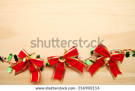 Christmas Red Bow ribbon over wooden background with copy space - stock photo