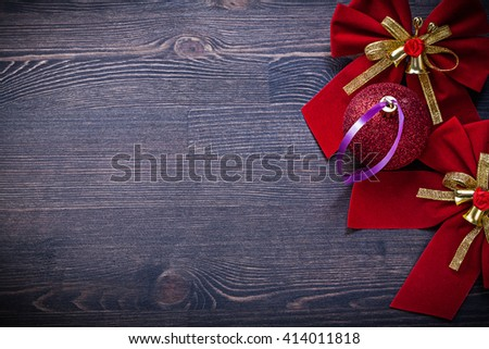 Christmas red bows ball on wooden board holidays concept. - stock photo