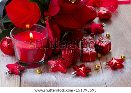 christmas red burning candle  with  decorations on wooden table
