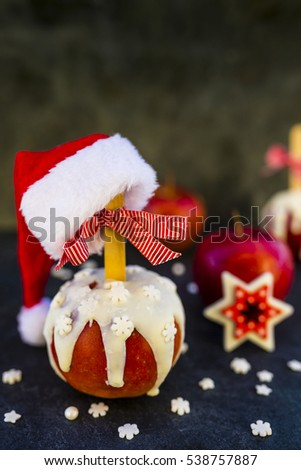 Christmas red delicious apples in white chocolate and Christmas decoration on dark background.