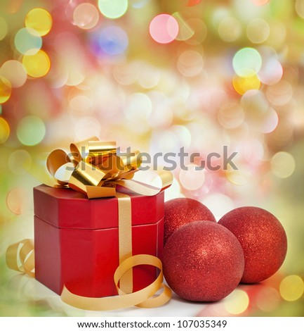 Christmas red gift and baubles against colorful blur background