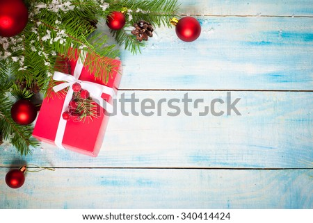 Christmas red gift box with a white ribbon and decorations on a blue background. Top view, copy space. - stock photo