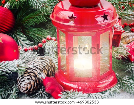 christmas red glowing lantern close up  with evergreen tree and snow close up