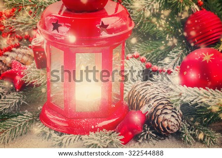christmas red glowing lantern close up  with fir  tree and falling snow, retro toned