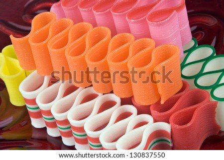 Christmas ribbon candy served on a red glass plate. Christmas theme. - stock photo