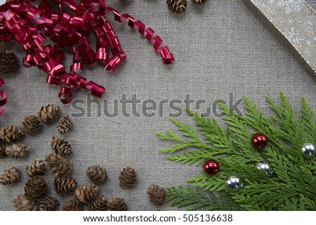 Christmas ribbons and pine cones on linen background with copy space