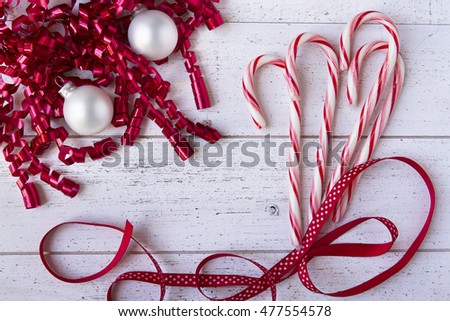 Christmas ribbons, ornaments and candy canes on white wooden table with copy space.