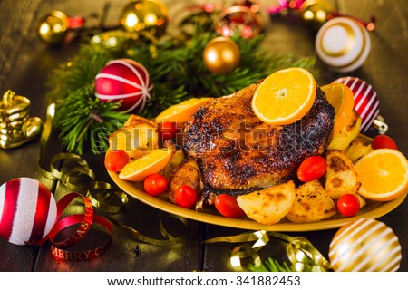 Christmas roast duck served with potatoes, orange and tomatoes on wooden festive decorated table