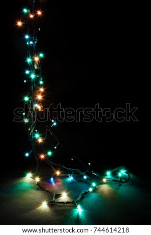 Christmas romantic lights frame on black background with copy space. Decorative garland in night space. Clear perfect beautiful decoration for intimate evening dinner. Studio close up photo. Seamless.