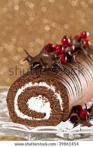 Christmas roulade decorated with chocolate dipped holly leaves - stock photo