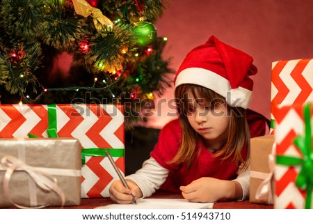 Christmas routine. Portrait of a serious little girl in a red dress and Santa Claus hat lying on the floor under the Christmas tree writing a letter