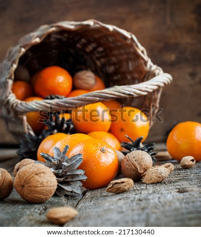 Christmas Rural Scene with Tangerines, Basket, Nuts, Pine cones, Walnuts and Almonds on wooden background. Vintage  - stock photo