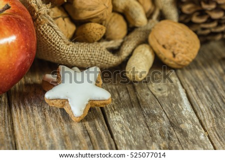 Christmas sack with nuts, cookies, red apple and pine cone on wooden table with copy space.
