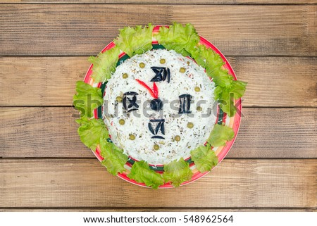 Christmas salad rice olives greens peas - concept New year clock, midnight, brown wooden background.