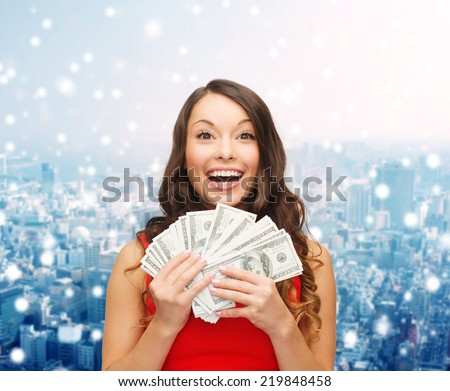 christmas, sale, banking, winning and holidays concept - smiling woman in red dress with us dollar money over snowy city background - stock photo