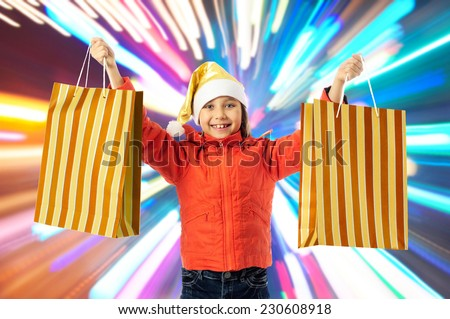 Christmas sales. Little girl with shopping bags - stock photo