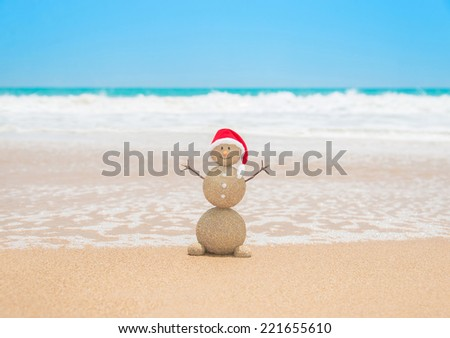 Christmas sandy snowman in red santa hat at tropical beach. Holiday concept for New Years Cards. - stock photo